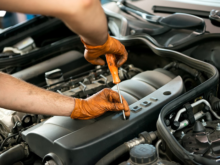 Close up of the gloved hands of a male mechanic working on a car engine with a screw driver in a workshop during a service